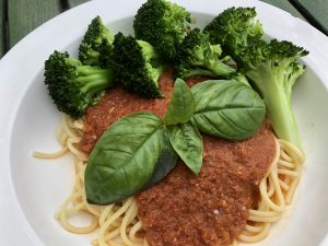 Tomato pesto sauce over pasta with steamed broccoli