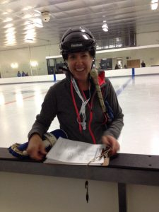 Jean LaMantia, writer of the 10 tips for a healthy lifestyle is wearing hockey helmet with coach's whistle around her neck and holding hockey stick on the ice at hockey arena