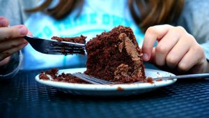 person in front of half eaten chocolate cake