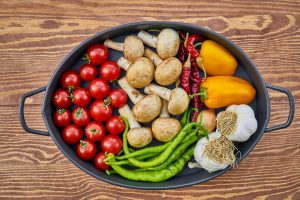 An oval roasting pan with cherry tomatoes, mushrooms, green beans, garlic, chilli peppers and yellow sweet peppers