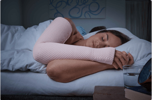 woman sleeping on bed wearing pink compression sleeve