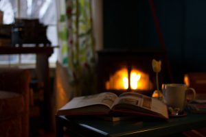 a book on a table in front of a fireplace with a fire