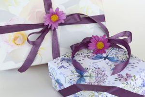 two gifts wrapped with brown ribbon and flowers