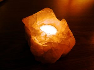 salt lamp with candle in dark room