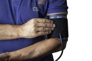 man in blue shirt with blood pressure cuff on arm
