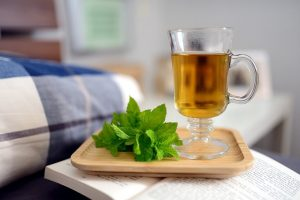 Tea in a clear mug with fresh mint leaves on tray