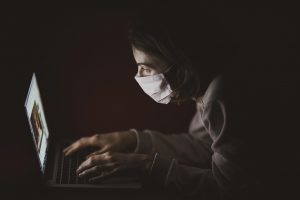 woman in dark with medical mask and gown looking at laptop