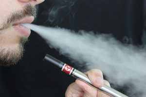 man exhaling vapour from an e-cigarette