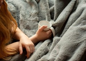 overhead view of woman's hands holding mug over grey fuzzy blanket