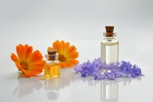 two small glass bottles with corks, orange flowers and purple flowers