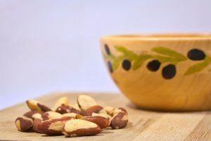 Brazil nuts on cutting board beside bowl