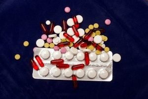 one blister pack of white pills and coloured pills on top