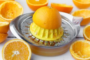 Half and orange on a manual juicer surrounded by orange halves