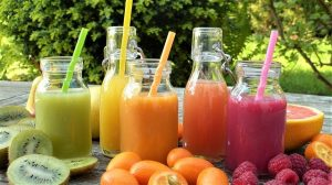 Bottles of juice with straws and fruit
