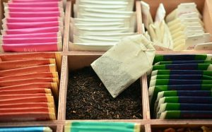 Black tea leaves in a tea box beside other packaged teas