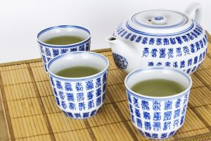 Blue and white teapot and matching 3 mugs with green tea