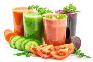 Glasses of juice and slices of vegetables